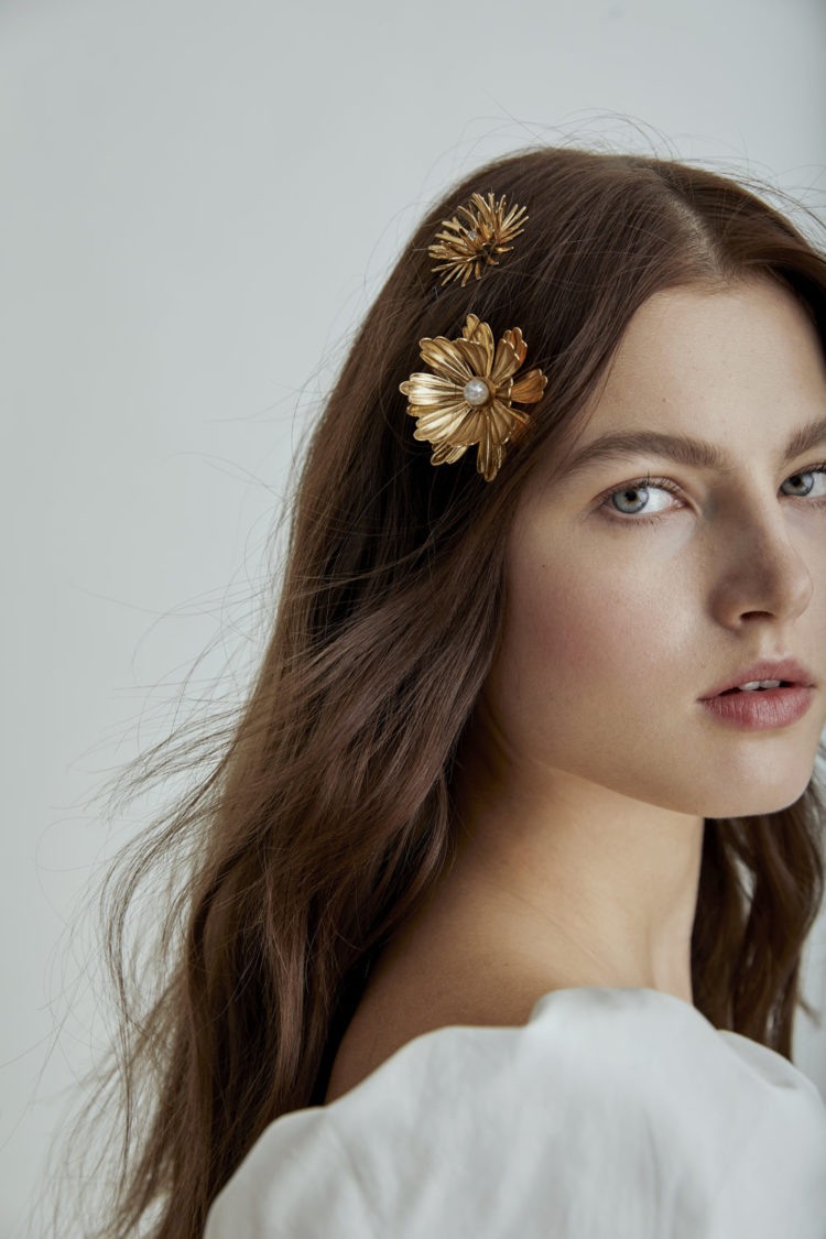 loose waves with gold flower hair pins that add a refined and chic touch to the simple hairstyle