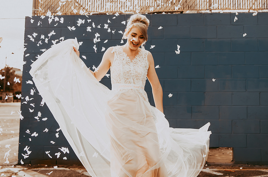 The bride chose a pale pink wedding dress with a lace no sleeve bodice and a layered skirt