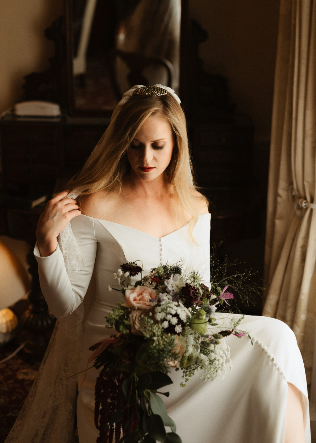 The bride was wearing a plain off the shoulder wedding dress with long sleeves and a button row plus a lace veil