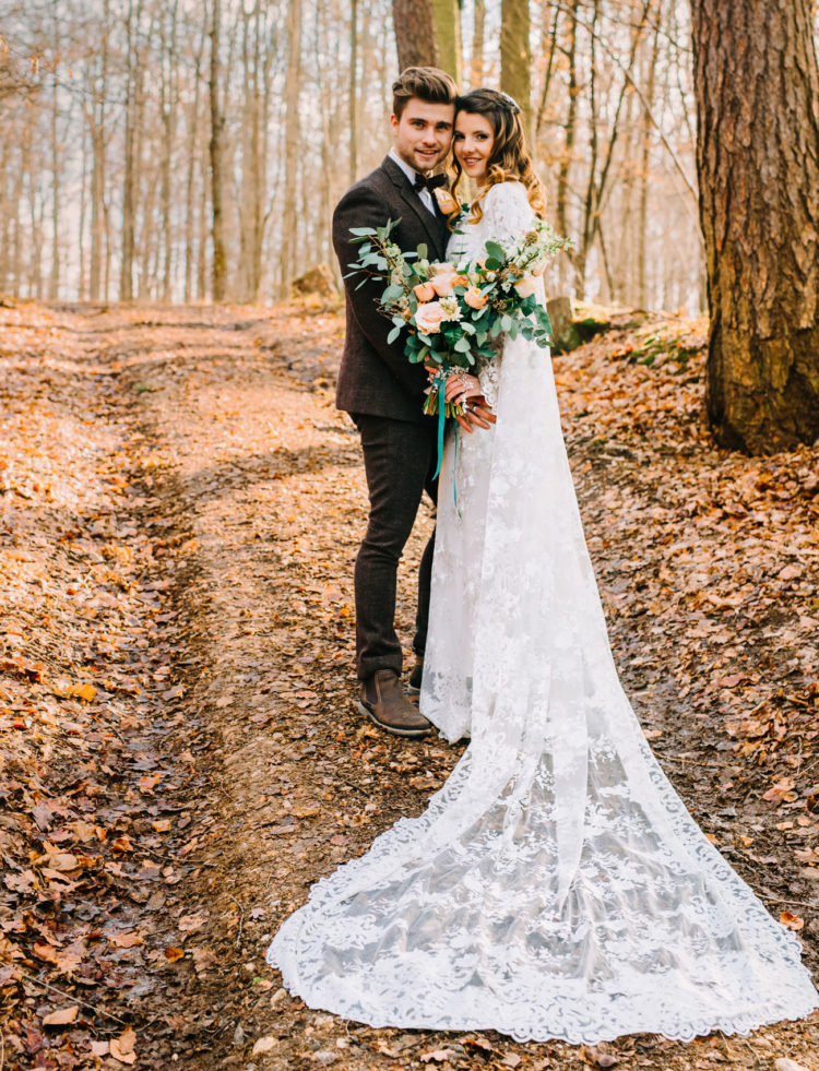 The bride was wearing a lace sheath wedding dress with a cape and a half updo, the groom was wearing a brown tweed three-piece suit with a bow tie and brown shoes