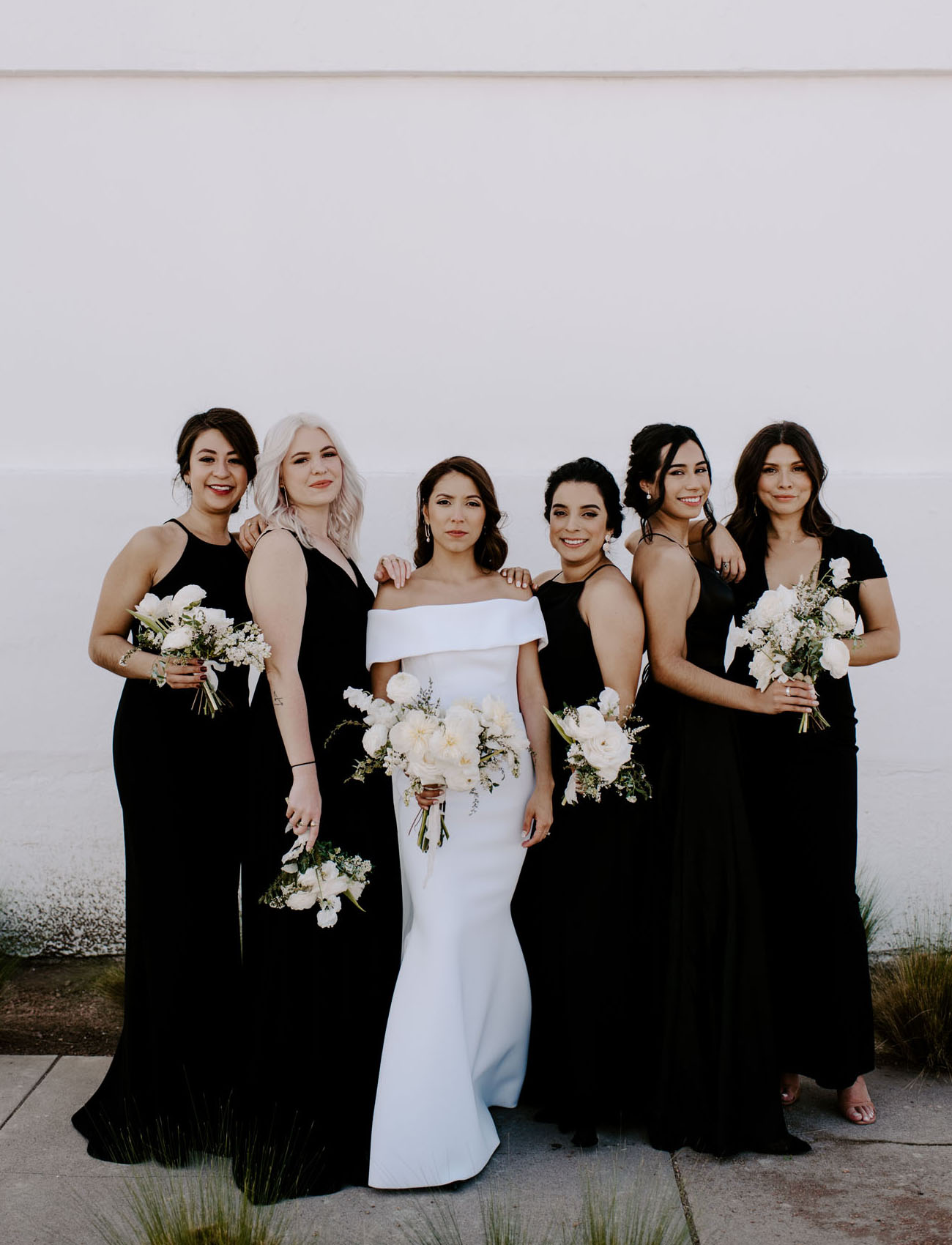 The bride was wearing an off the shoulder sheath wedding dress, the bridesmaids were rocking mismatching black gowns