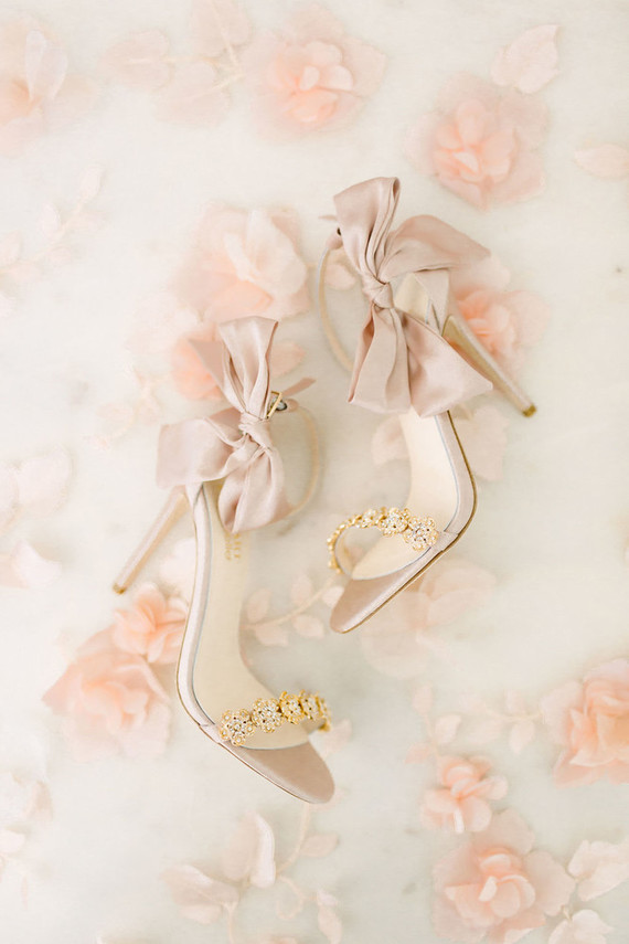 The bride was wearing chic blush heels with embellishments and large fabric bows