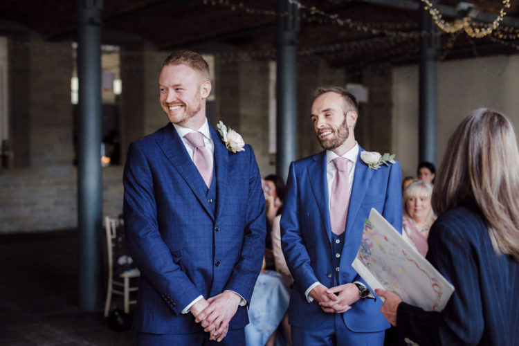 The grooms were wearing three-piece bold blue wedding suits and pink ties, all of them were custom-made for the couple