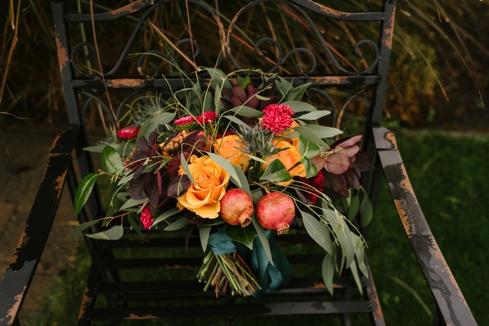The wedding bouquet was done with much greenery, marigold and fuchsia blooms, berries and pomegranates