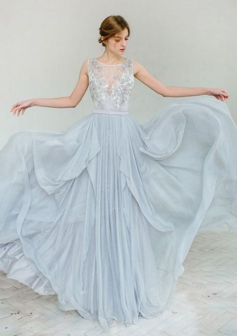 a beautiful light blue sleeveless wedidng dress with embroidery and beading on the bodice, an illusion neckline and a layered skirt