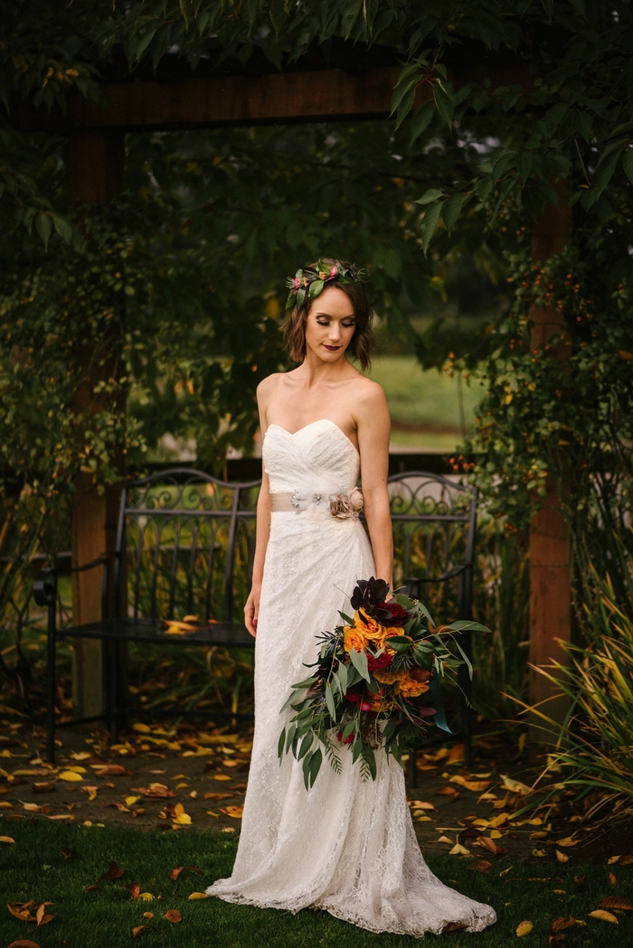 The bride was wearing a strapless lace wedding dress with a sash with fabric blooms, a floral crown and a dark lip