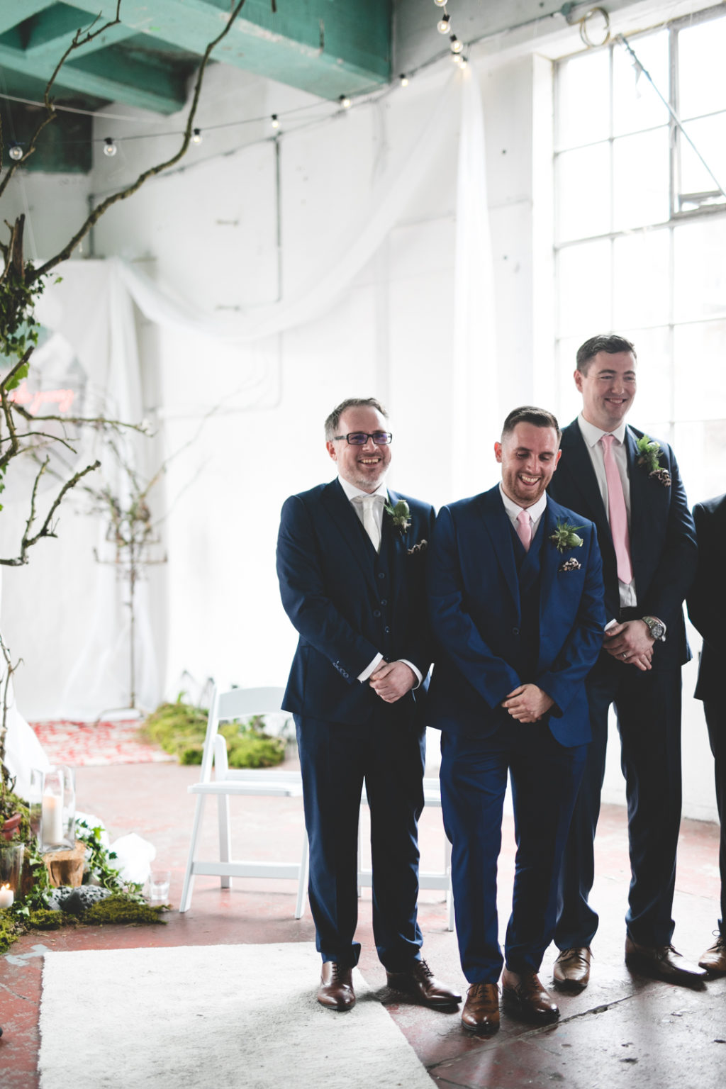 The groom and groomsmen were wearing blue and navy three piece suits with various ties