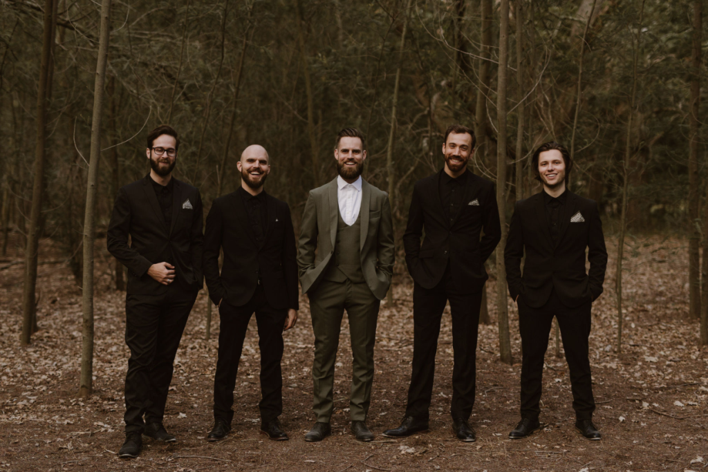 The groom was wearing an olive green three piece suit, and the the groomsmen were rocking all black