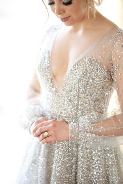 a beautiful silver fully embellished wedding dress with a deep V-neckline and matching earrings