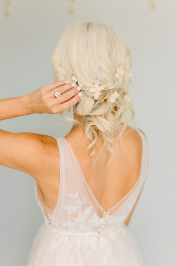 The bride was wearing a wavy updo with blush blooms and a blush A-line wedding dress with floral appliques