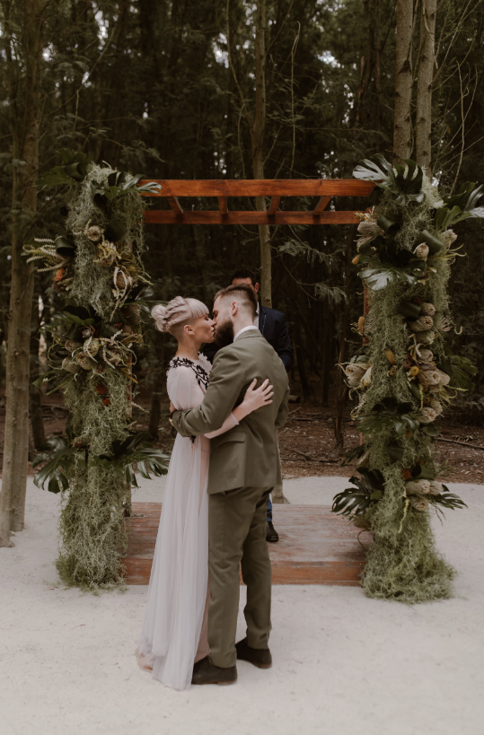 The wedding arch was done with greenery, moss, monstera leaves, antlers and king proteas