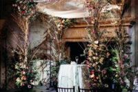 05 The wedding arch was lusly decorated with blooms and twigs, with an airy fabric piece on top