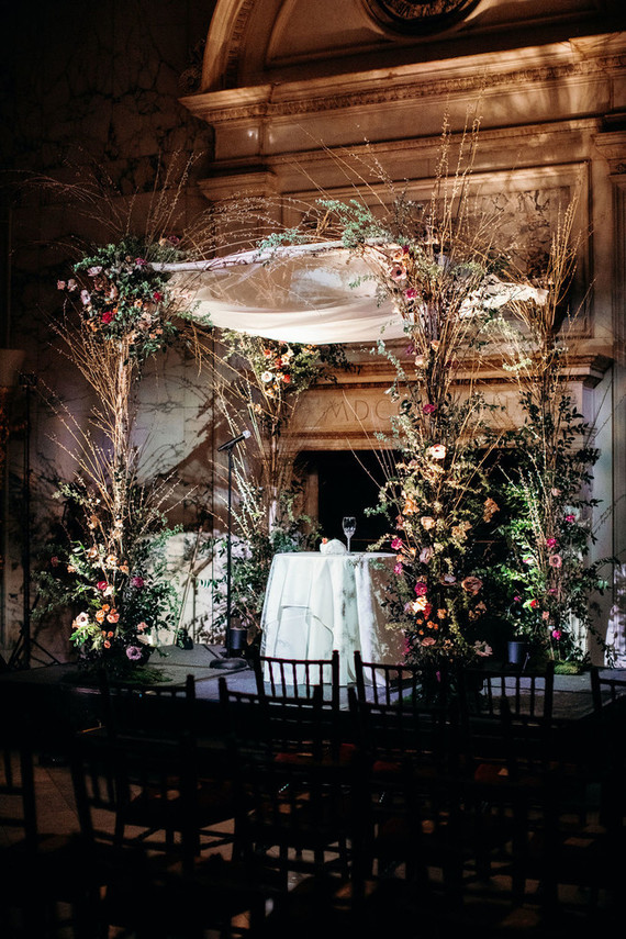 The wedding arch was lusly decorated with blooms and twigs, with an airy fabric piece on top