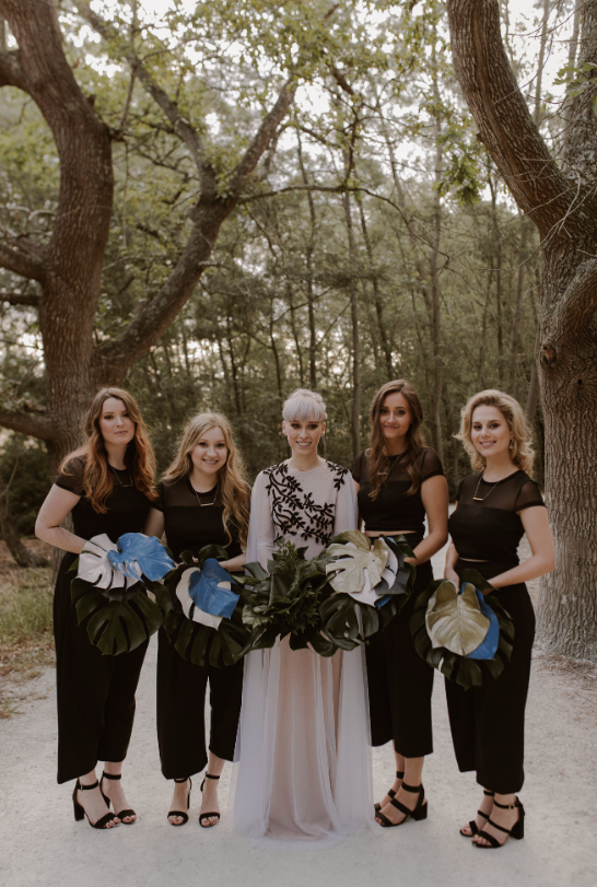 The bridesmaids were rocking black illusion neckline tops and cropped pants plus monstera leaf bouquets