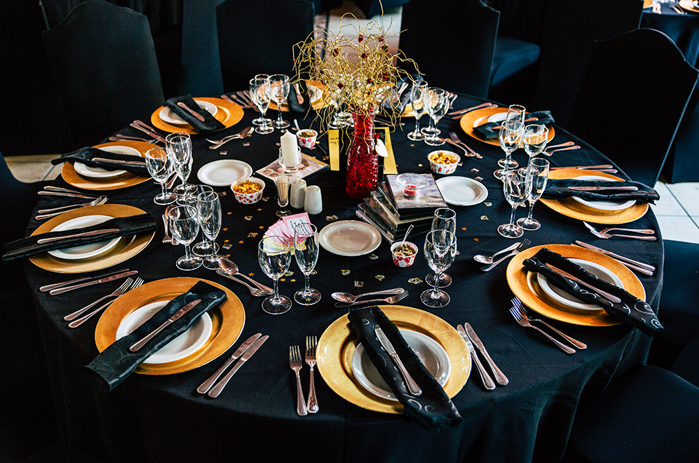 The wedding tables were styled in black and marigold, with a quirky centerpiece in a red vase and rhinestones and stars