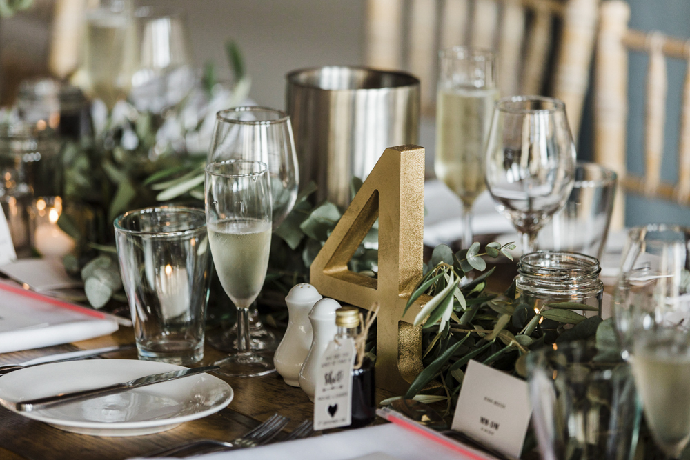 The wedding tables were styled with greenery, gold numbers, neutral cutlery and porcelain