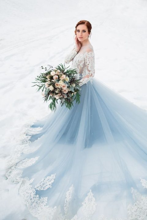 a breathtaking wedding dress with a white lace bodice and a blue skirt with white lace and a train