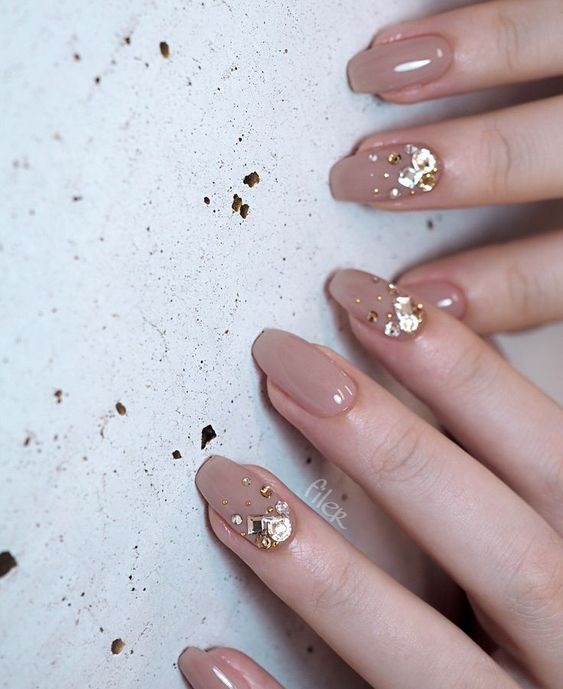 a grey wedding manicure highlighted with large gold rhinestones for a refined bride