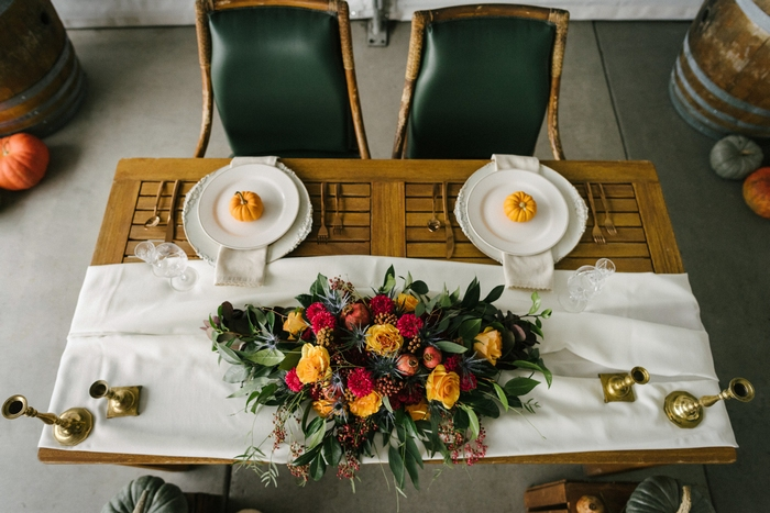 The sweetheart table was done with neutral fabric, rich tone blooms and greenery, gildd candleholders and pumpkins for marking place settings