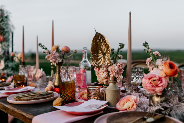 The wedding tablescape was done in pink and peachy pinks, with gilded blooms, amber glasses and wooden boards