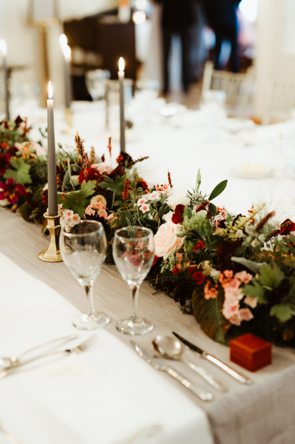 The wedding tablescape was done with bright and blush blooms and greenery, with grey candles and neutral tablecloths