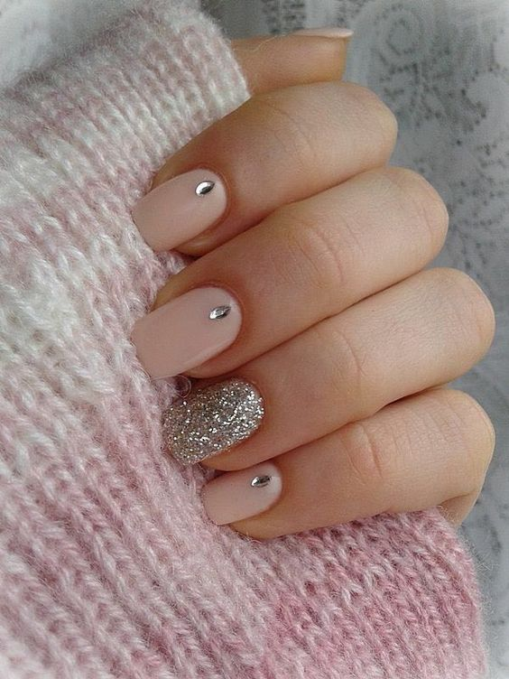 a shiny blush wedding manicure with rhinestones and a silver glitter ring finger for a chic and glam look
