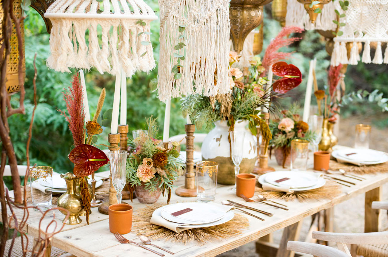 Candles, dried herbs and blooms, pampas and terracotta cups create a boho feel at the table