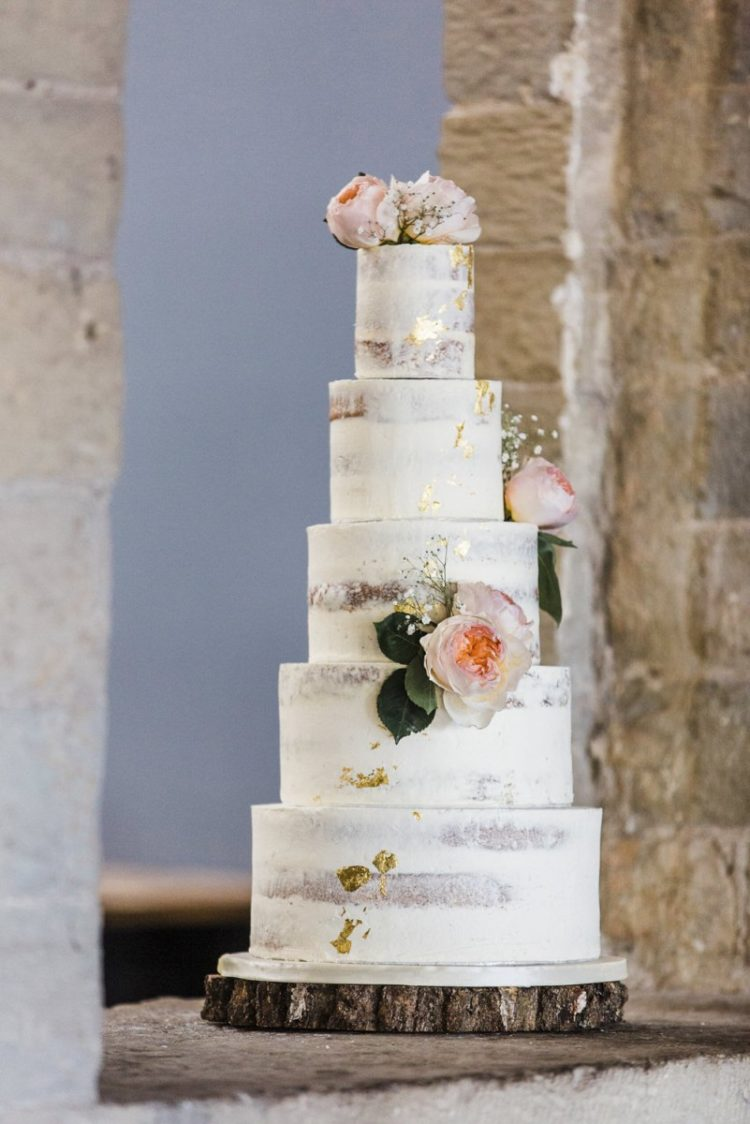 The wedding cake was naked, with gold leaf decor and pink blooms and foliage for a cozy feel