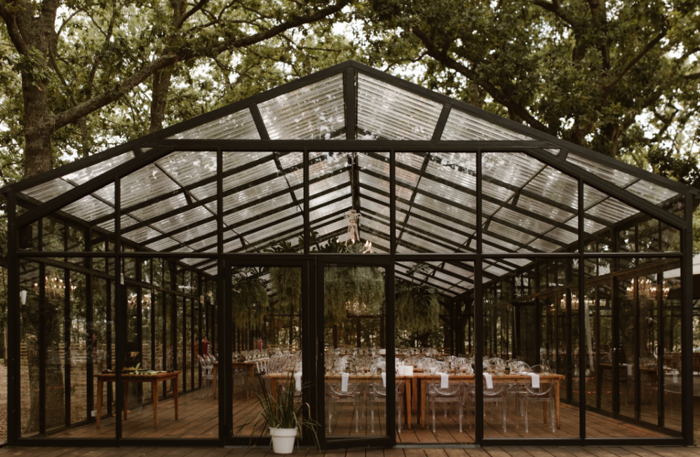 The wedding reception took place in a glasshouse that was opened to outdoors as much as possible