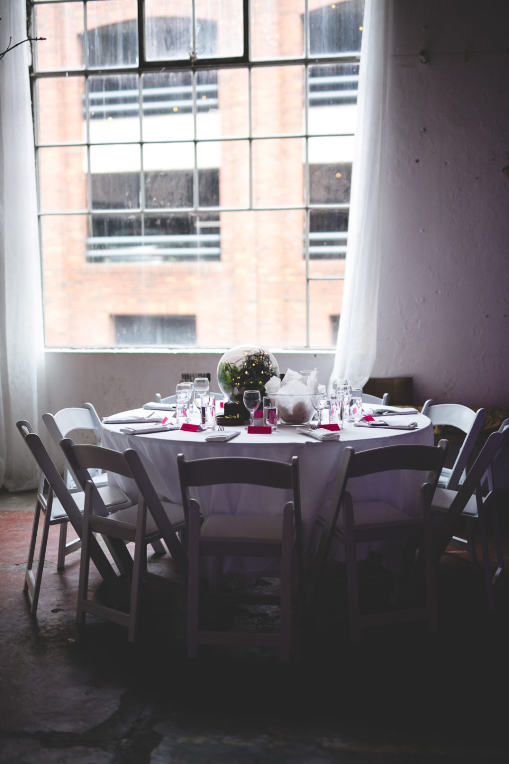 The wedding tables were done with greenery and lights, bright fuchsia touches