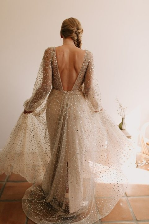 a tan fully embellished wedding gown with an open back, a train and a V-neckline