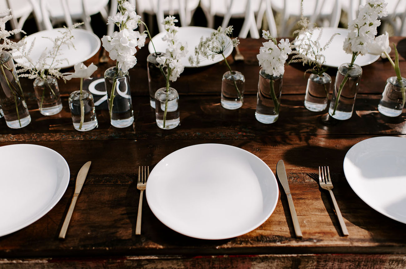 The wedding reception tables were done with white blooms in sheer vases and gold cutlery