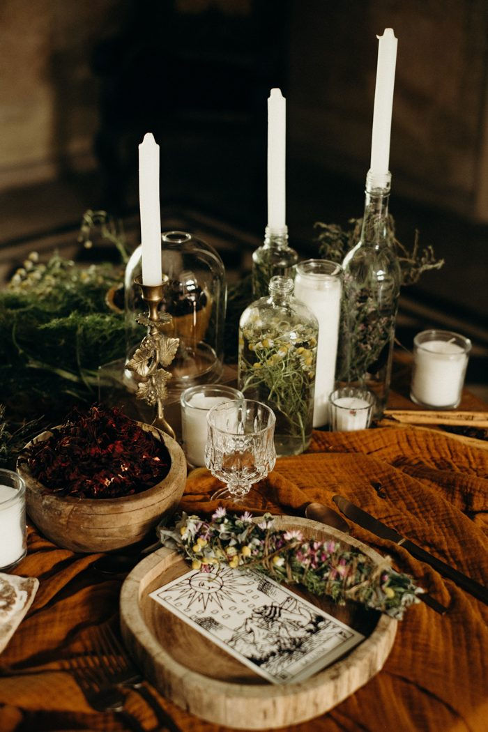 The wooden plates were topped with herbs, there were candles and rust linens on the table