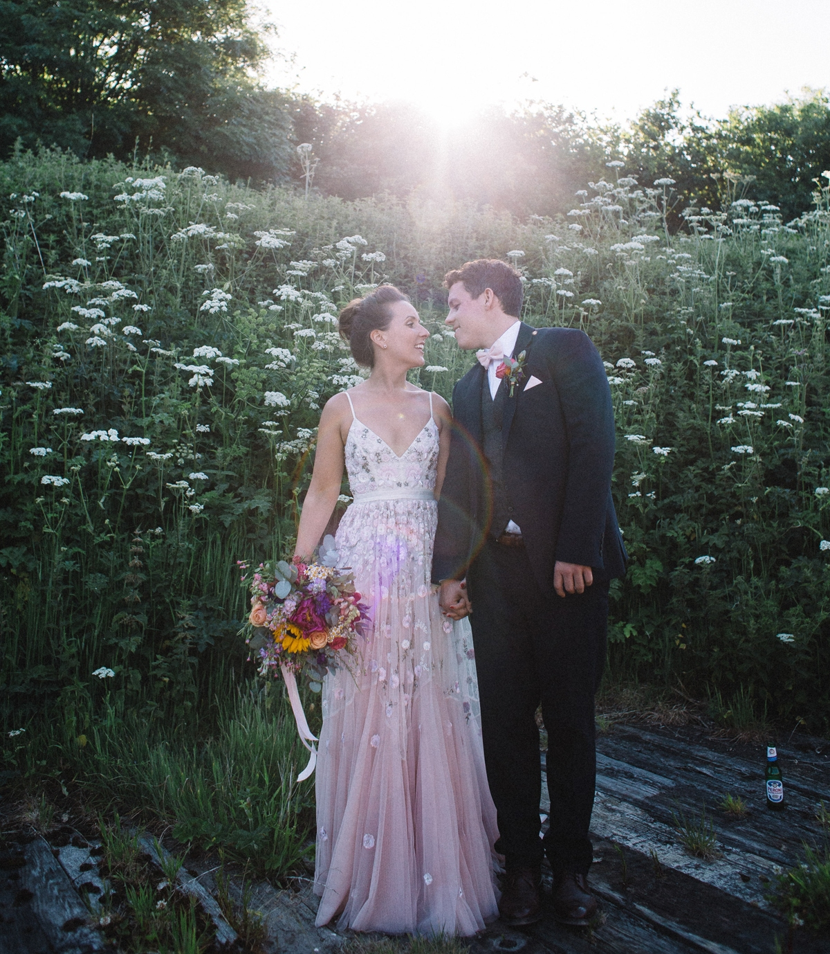 a pink spaghetti strap wedding dress with floral appliques and embroidery plus a highlighted waistline