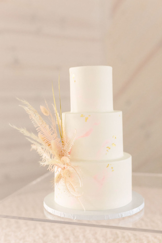 The wedding cake was a neutral one with pink touches and gold leaf plus dried herbs