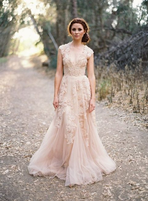 a sleeveless blush pink wedding dress with lace appliques that add a trendy touch and a deep V-neckline