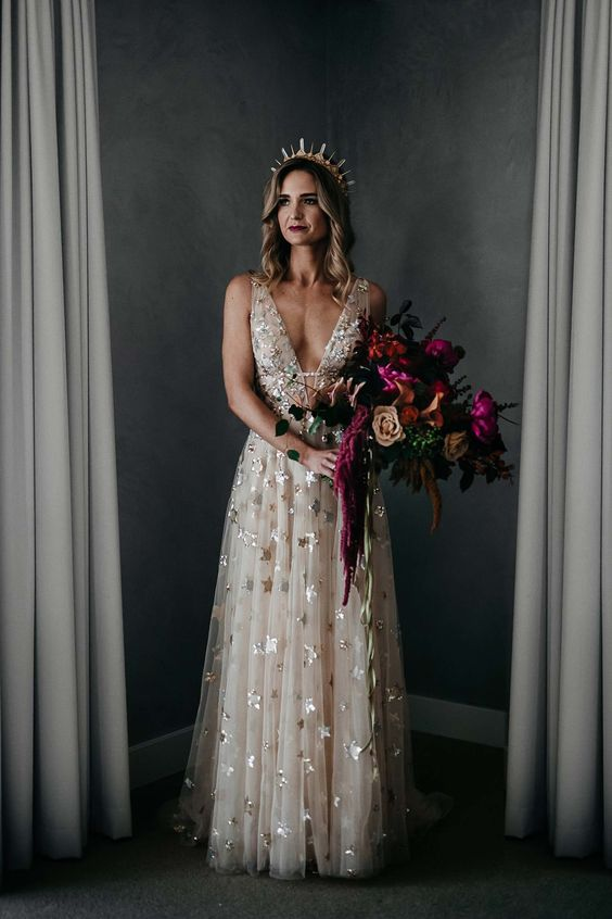 a blush thick strap wedding dress with foil stars and a plunging neckline plus a crystal crown for a celestial bride