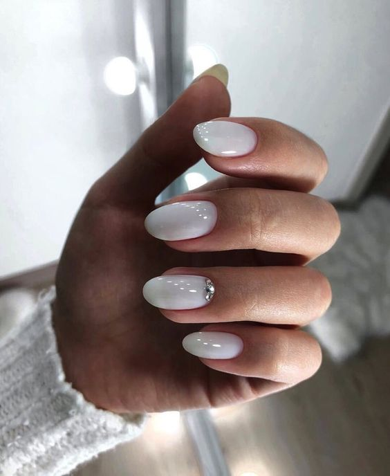 shiny white nails with a large rhinestone on the ring finger is a chic idea for a bride who loves glam