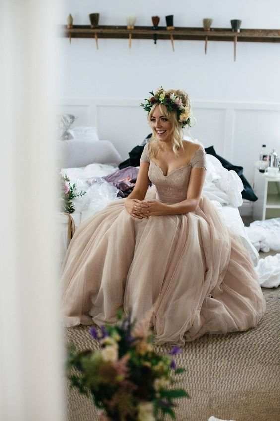 a dusty pink off the shoulder wedding dress with cap sleeves, a deep cut neckline and a layered skirt