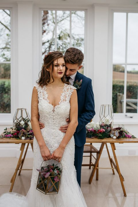 a lace sheath wedding dress with a V-neckline, no sleevess and a train plus a dark lip is a super romantic option