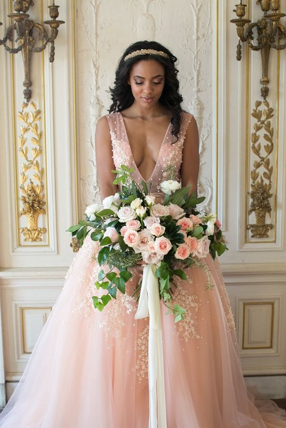 a gorgeous pink princess style wedding dress with a plunging neckline, beading and white floral lace appliques