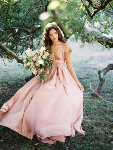 a pink silk A-line wedding gown with thick straps and a plunging neckline is ultra-modern yet very romantic