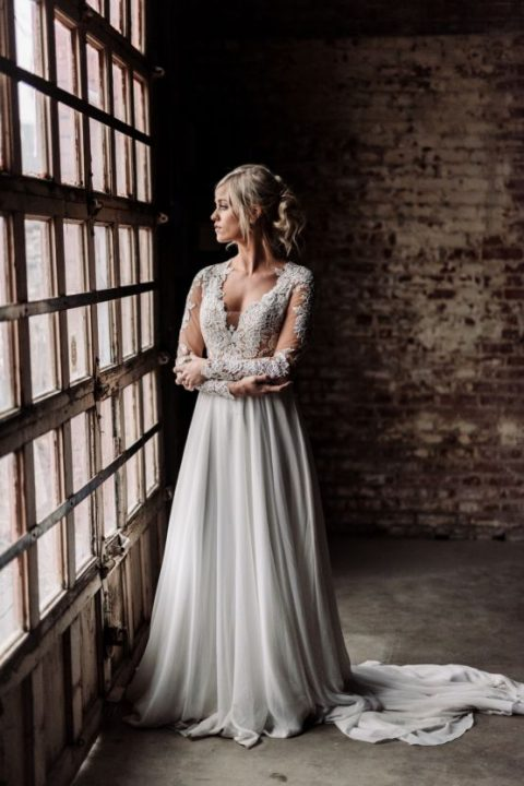 a wedding gown with a lace bodice with an illusion plunging neckline, long sleeves and a flowy skirt with a train