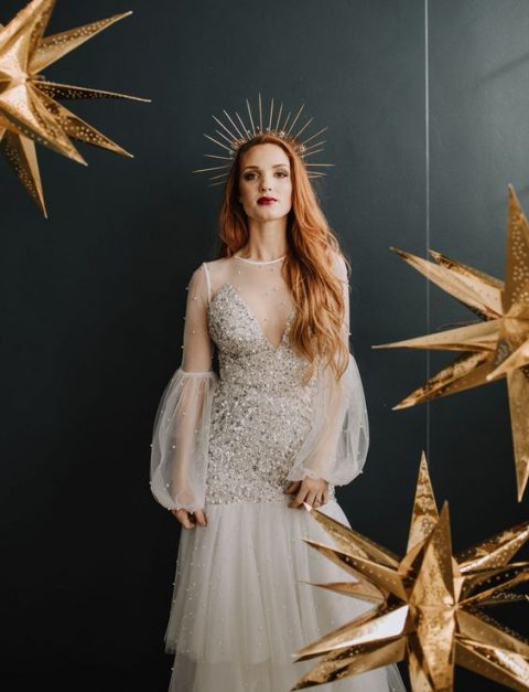 a whimsy wedding dress with silver sparkles, puff sleeves, a layered skirt plus a sunburst crown