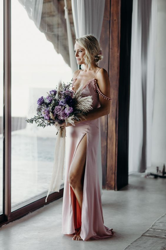 Malin Akerman wearing a pink silk spaghetti strap wedding dress with pompom detailing and a front slit for a modern and boho feel