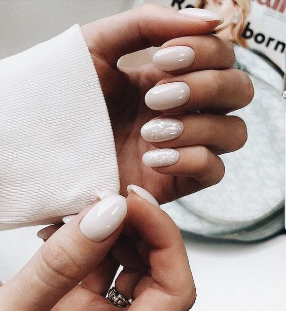 shiny white nails and two accent ones with a touch of mother of pearl look very feminine and chic