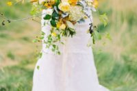 a bold marigold wedding bouquet with lush blooms, some fall ried leaves and fresh greenery for a fall wedding