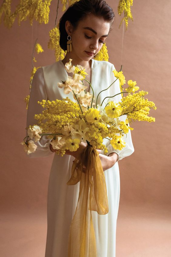 a bold yellow wedding bouquet composed of various types of flowers and decorated with long yellow ribbons