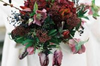 a burgundy wedding bouquet with mauve blooms and privet berries is a stylish option for a winter wedding