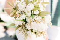 a chic white wedding bouquet with just some touches of foliage is a very stylish idea for a romantic bride